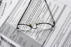 Read. Close up of Real Estate contract with reading glasses stock image