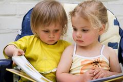 Read. Two small friends sit outside on a chair and read together a book Stock Photography
