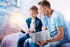 Delighted male person reading task. Read it. Attentive dad holding laptop and turning head while listening to his son Royalty Free Stock Photography