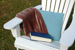 Read a book. Adirondack chair with pillow blanket and book Stock Images