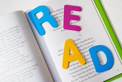 Read a Book. Read to or with, it doesn't matter just read.  Educational or recreational theme.  Letters on top of a children's book that I wrote and published Royalty Free Stock Photo