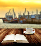 Read book with coffee cup beside jetty Royalty Free Stock Photography