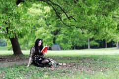 Read a book sitting under a blossom tree stock photography