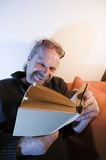Read in the book wide. Older man sitting in a shadowed corner of a room reading a book Royalty Free Stock Images