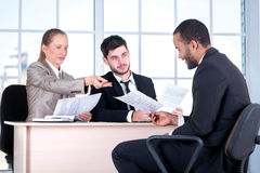 Read the contract. Three successful business people sitting in t Royalty Free Stock Photo