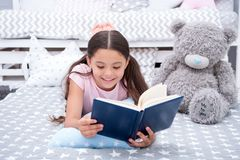 Read fairytale in bed. Girl child lay bed with teddy bear read book. Kid prepare to go to bed. Time for evening. Fairytale. Girl kid long hair cute pajamas stock photos