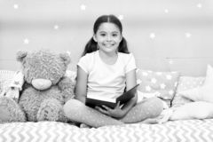 Read fairytale before go to bed. Girl child sit bed with teddy bear read book. Kid prepare to go to bed. Pleasant time. In cozy bedroom. Girl kid long hair cute stock image