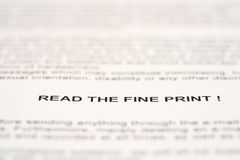 Read the fine print. Text on a page of paper warning to read the fine print on documents royalty free stock photo