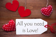 Read Hearts, Label, Quote All You Need Is Love. Label With English Quote All You Need Is Love. White Label With Red Textile Hearts. Retro Brown Wooden Background Royalty Free Stock Photography