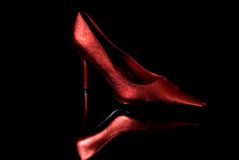 Read heat. Red high heel shoes reflected on the black background stock image