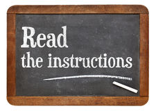 Read the instructions advice. On a vintage slate blackboard Royalty Free Stock Photo