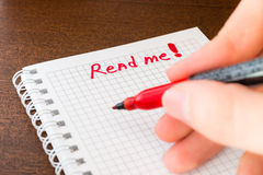 Read me sign in the notebook by red marker in the hand Royalty Free Stock Photo