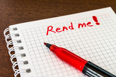 Read me sign in the notebook by red marker Royalty Free Stock Photo