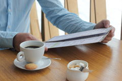 Read the menu in the cafe. Man drinking morning coffee in the cafe and read the menu. morning with a cup of coffee Royalty Free Stock Images