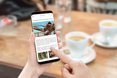 Read news article with smart phone. News portal web site with business information royalty free stock images