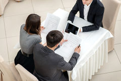 Read the rules! Three young businessman sitting at a table in th Stock Images