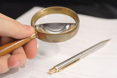 Read before sign. Hand holding magnifying glass over document Stock Image