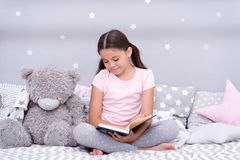 Read before sleep. Girl child sit bed with teddy bear read book. Kid prepare to go to bed. Pleasant time in cozy bedroom. Girl kid long hair cute pajamas relax stock images