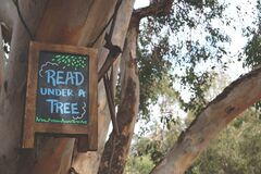 Read Under a Tree Signage Hanging on Branch Tree Stock Photos