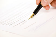 Read and understood signature. Someone signing a document with a pen. Text is blur, only read and understood is visible. Isolated on white background royalty free stock photography