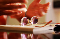 Reader Accessories. A reading picking up his glasses to read a book Royalty Free Stock Image