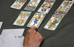 Reader's hand during the reading of the playing cards and Taro Stock Photo