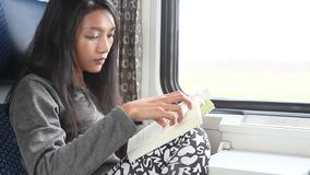 Reader in train. Young Asian woman read her book while traveling by train stock video footage