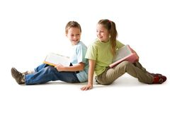 Readers. Portrait of cute schoolchildren sitting on the floor with open books Royalty Free Stock Photo