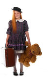 Readhead girl is ready to travel. Readhead girl in an old style dress with her toy bear and trunk ready to travel stock photo