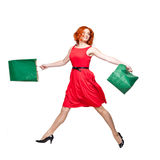 Readhead with green shopping bags jumping Royalty Free Stock Photo