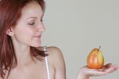 Readhead health & beauty 1. Young red-haired girl holding a ripe pear stock image