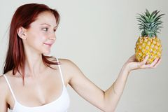 Readhead health & beauty 2. Young beautiful red-head holding a pineapple royalty free stock photos
