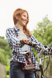 Readhead standing next to her bike with a camera Royalty Free Stock Photography