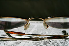 Readind a book. Glasses sitting on a top of a book royalty free stock image