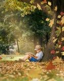 Readind de garçon sous le grand arbre de tilleul Photographie stock