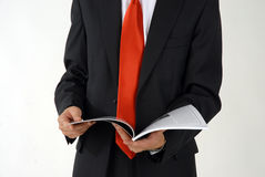 Reading. Business men reads magazine. He wears red tie abd black suite stock photography