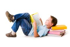 Reading. Image of schoolboy lying with his head on the heap of books and reading one of them Stock Photography