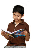 Reading. An adorable boy reading his school book Royalty Free Stock Photography
