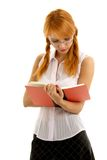 Reading. Lovely redhead reading red book Stock Photos