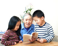 Reading. Grandpa is reading to his grandchildren Stock Images