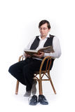 Reading. Man in glasses sits on chair and reads book Royalty Free Stock Image