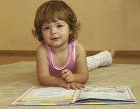 Reading. Little girl lying on the carpet and reading a fairy tale Stock Photography