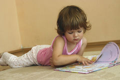 Reading. Little girl lying on the carpet and reading a fairy tale Royalty Free Stock Photography