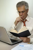 Reading. A businessman reads a book as he sits at his laptop.. Space for text on the white background Stock Photography