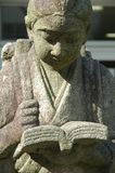 Reading. Statue of a Japanese student concentrating in his reading Royalty Free Stock Image
