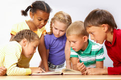 Reading. Portrait of pupils looking at page of encyclopaedia at reading lesson Stock Photos