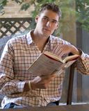 Reading - 16. Young man sitting by natural window light reading Royalty Free Stock Photo