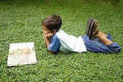 Reading. Child reading a book on the lawn Stock Photography