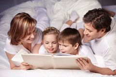 Reading. Parents with children are reading Stock Photography
