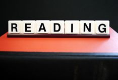 Reading. Letters spelling reading on top of a book Stock Image